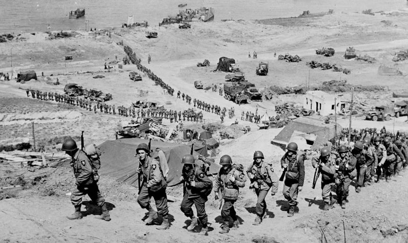 Войска 2-й пехотной дивизии армии США проходят возле немецкого бункера. Омаха-Бич. Июнь, 1944 г.