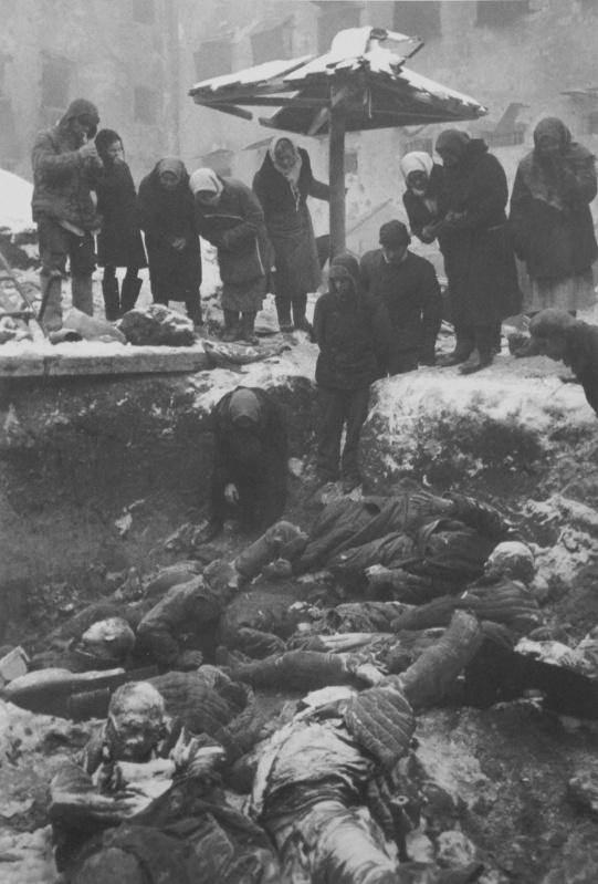 Жители во дворе тюрьмы гестапо опознают родственников, убитых немецкими оккупантами. Февраль 1943 г.