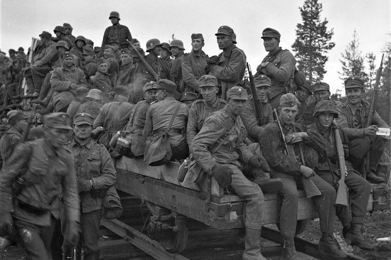Финские солдаты и солдаты войск СС перемещаются по узкоколейной железной дороге. Июнь 1944 г.