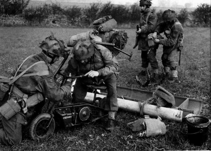 Британские парашютисты обучаются собирать мини-мотоцикл «Welbike», сброшенный в транспортном контейнере. Весна 1944 г.