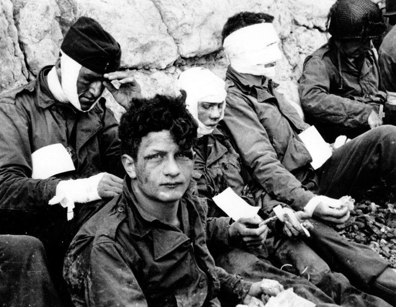 Раненные солдаты 1-й американской пехотной дивизии во время штурма Омаха-Бич. 6 июня 1944 г.