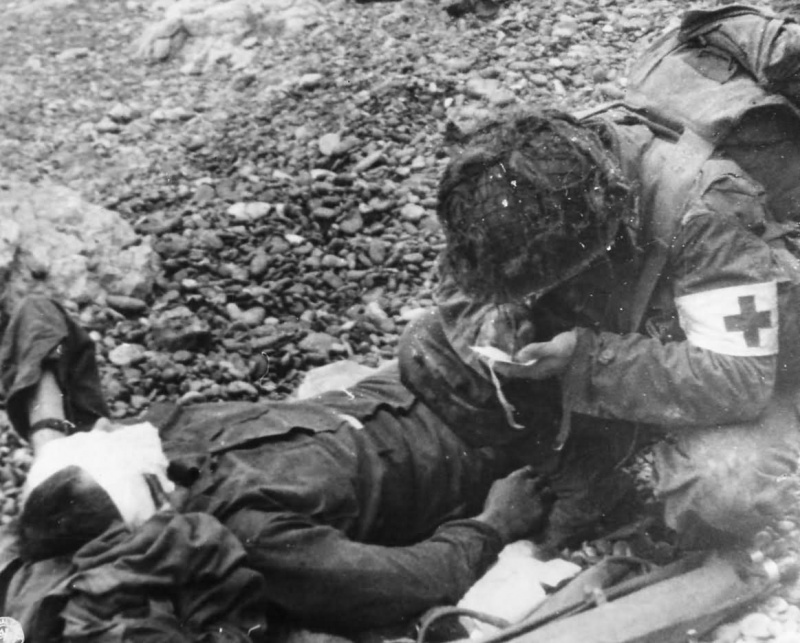 Медик 4-й американской пехотной дивизии оказывает помощь раненому солдату на Омаха-Бич. 6 июня 1944 г.