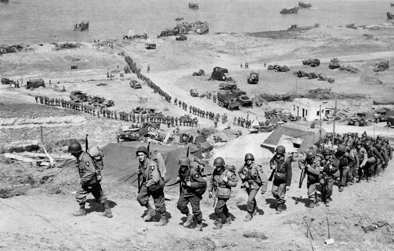 Американские солдаты поднимаются по склону на побережье Омаха. 6 июня 1944 г.