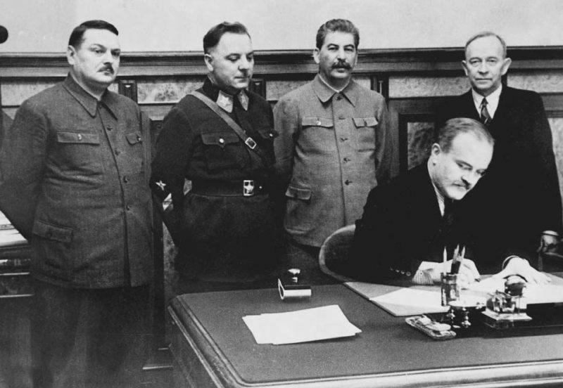 В. М. Молотов подписывает договор между СССР и Териокским правительством. Стоят: А.А. Жданов, К.Е. Ворошилов, И.В. Сталин, О.В. Куусинен. 2 декабря 1939 г.