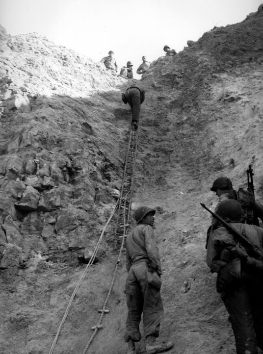Американские рейнджеры поднимаются по веревочной лестнице на мысе Пуант-дю-Хок. 8 июня 1944 г.