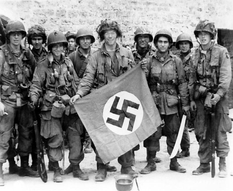 Американские десантники с захваченным нацистским флагом. Юта-Бич. 6 июня 1944 г.