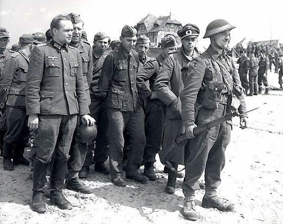 Пленные немцы под охраной канадского солдата. Курсель-сюр-Мер. 6 июня 1944 г.