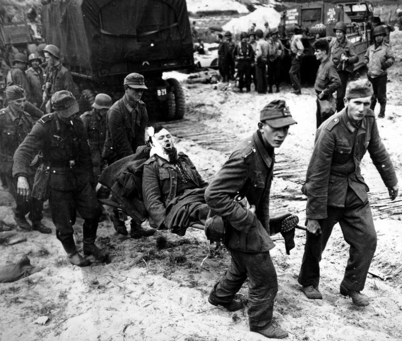 Немецкие военнопленные несут своих раненых в американский полевой госпиталь. Пляж Сен-Лоран-сюр-Мер. Июнь 1944 г.