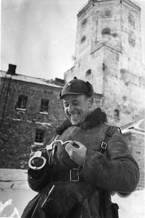 Советский офицер рассматривает финские наручники, найденные в Выборгском замке. Февраль 1940 г.
