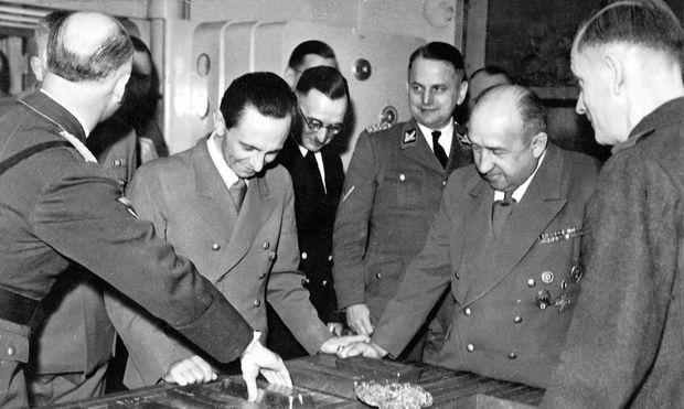Геббельс, президент Рейхсбанка Функ и группенфюрер СС Олендорф над слитками, выплавленными из золотых коронок и украшений погибших заключенных концлагерей.