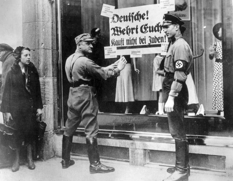 Плакат на витрине магазина гласит: «Немец остерегайся. Не покупай у евреев».