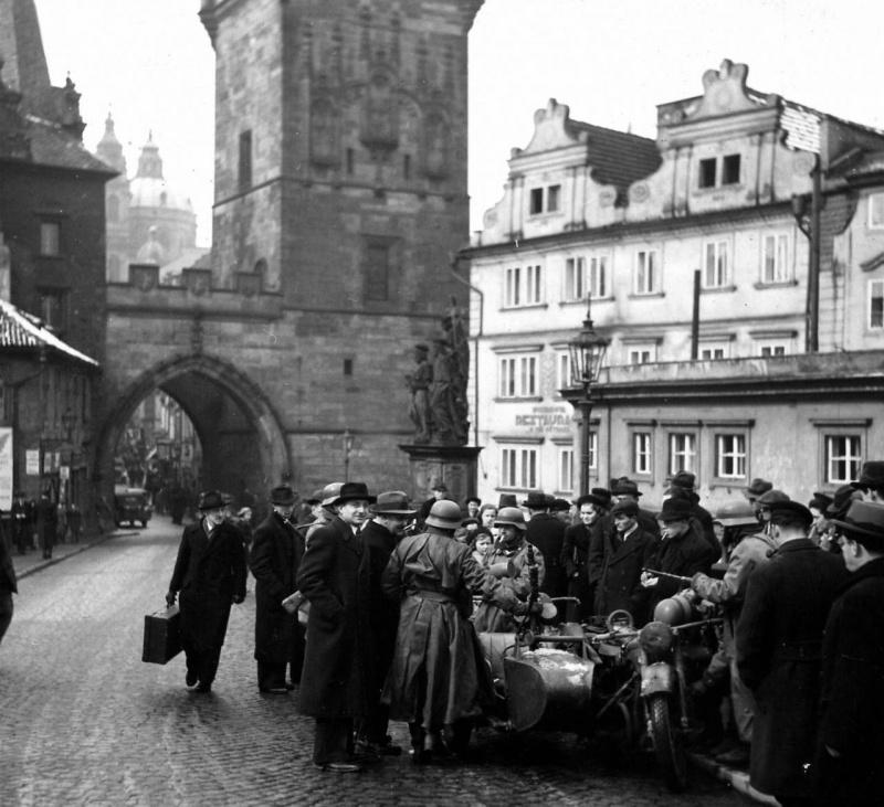 Немецкие мотоциклисты общаются с жителями Праги на Карловом мосту. Март 1939 г.