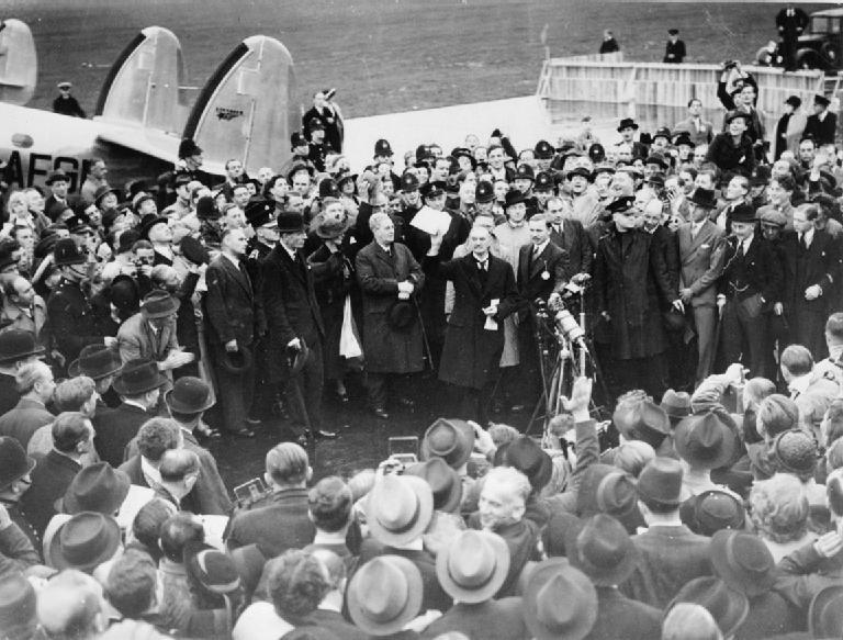 Невилл Чемберлен держит в руках документ, подписанный им и Гитлером по возвращении из Мюнхена на аэродроме Хестона.