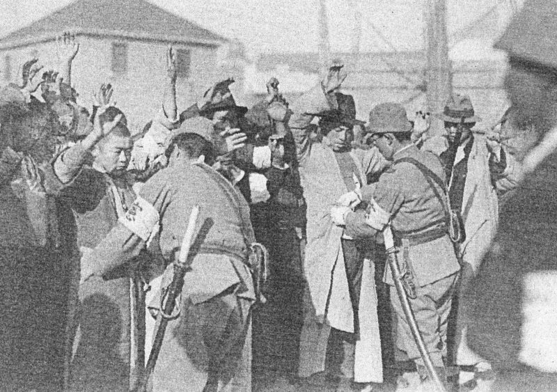 Японские солдаты обыскивают горожан.