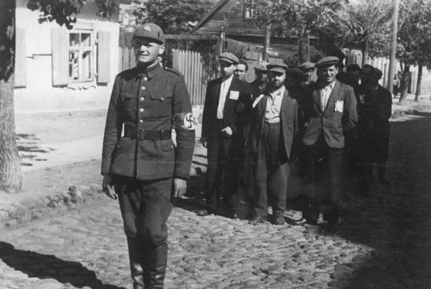 Литовский солдат с группой евреев, готовым идти на назначенную работу. Июль 1941 г.