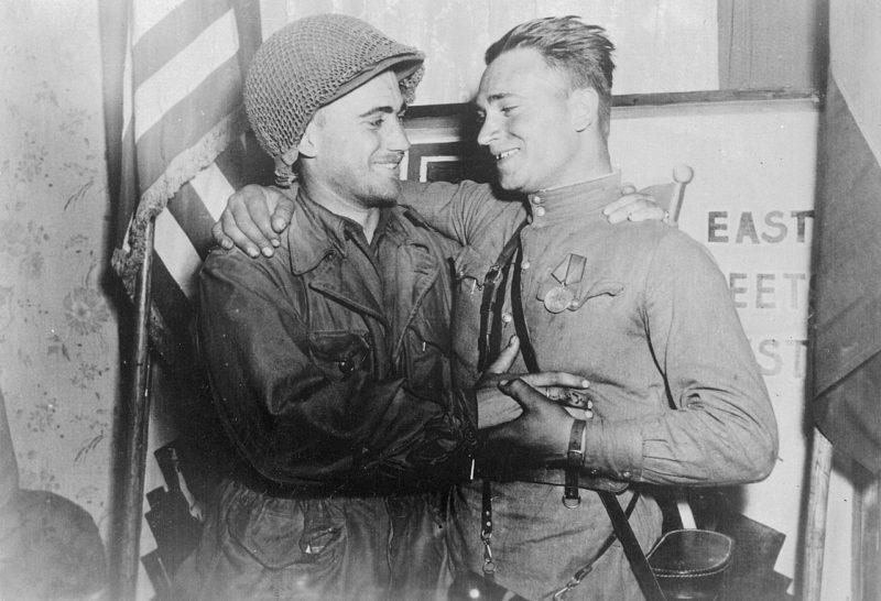 2-й лейтенант У. Робертсон и лейтенант А. С. Сильвашко на фоне надписи «Восток встречается с Западом», символизирующей историческую встречу союзников на Эльбе. 27 апреля 1945 г.