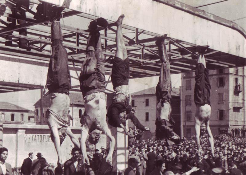 Труп Муссолини (второй слева) рядом с Петаччи (в центре) и другими казненными фашистами на площади Лорето.