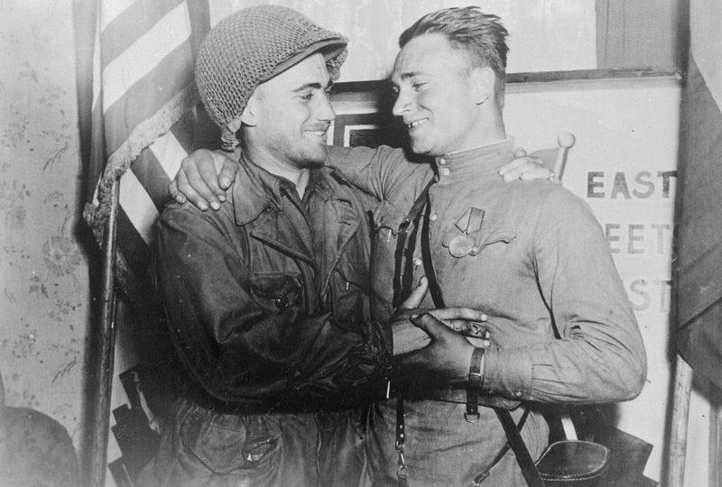 2-й лейтенант У. Робертсон и лейтенант А. С. Сильвашко на фоне надписи «Восток встречается с Западом», символизирующей встречу союзников на Эльбе. 25 апреля 1945 г.