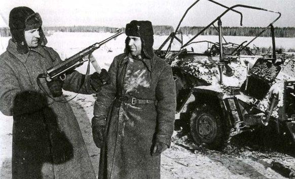 Красноармейцы рассматривают немецкие трофеи из подбитой бронемашины. Ноябрь 1941 г.