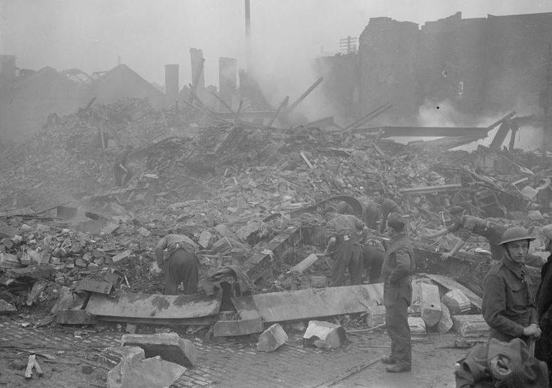 Военнослужащие вспомогательного военного корпуса разбирают дымящиеся завалы после бомбардировки. Ноябрь 1940 г.