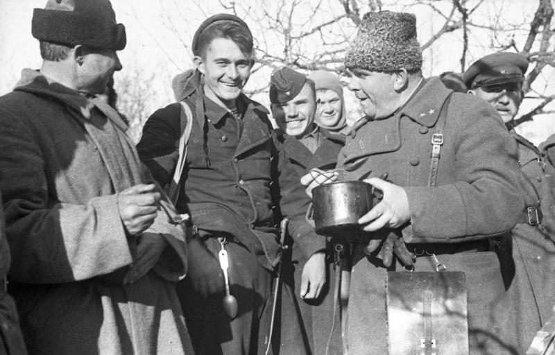 Командир 25-й стрелковой дивизии Приморской армии генерал-майор Т. Коломиец пробует обед на полевой кухне. Март 1942 г.