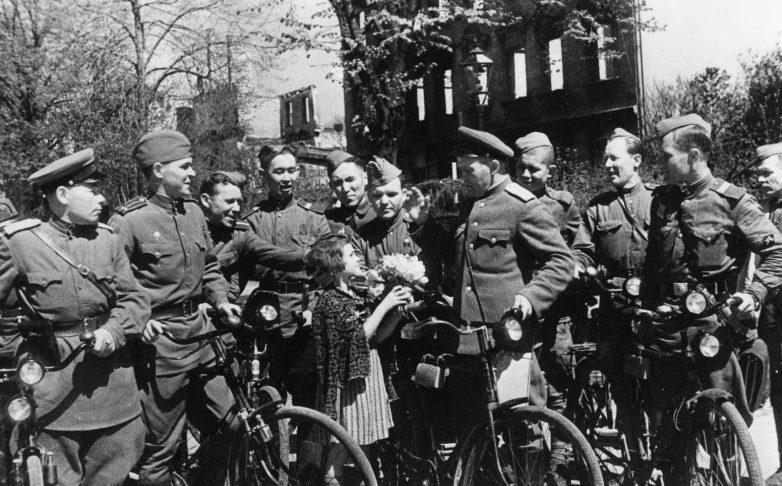 Немецкая девочка дарит цветы советским военнослужащим. Июнь 1945 г.