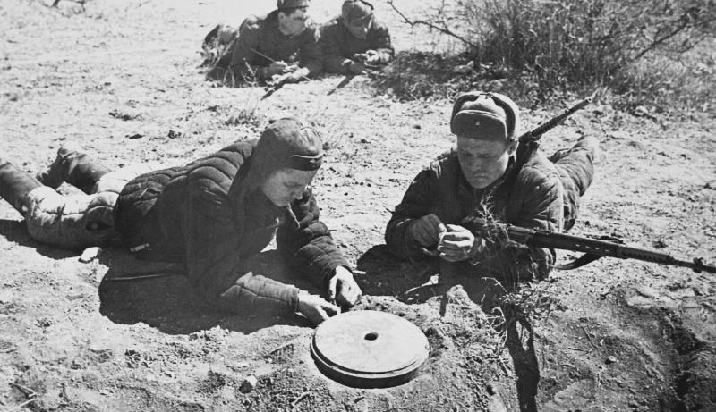 Советские саперы-разведчики обезвреживают немецкую противотанковую мину. 1942 г.