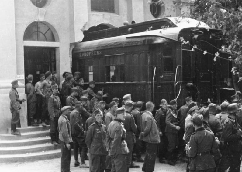 «Компьенский» вагон вывозят из музея сквозь пролом в стене.