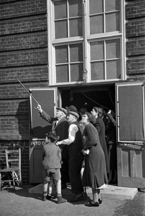 Жители Лондона наблюдают за немецкими самолетами у входа в бомбоубежище. 1940 г.