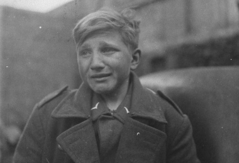 Пятнадцатилетний немецкий зенитчик Ганс-Георг Хенке, взятый в плен солдатами США в городе Рехтенбах. Германия. Март 1945 г.