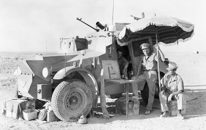 Британские офицеры 11-го гусарского полка с зонтиком во время перерыва в патрулировании на ливийской границе. 1940 г.