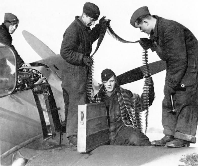 Немецкие оружейники заряжают пулеметы MG-17 истребителя Bf.109E. 1940 г.