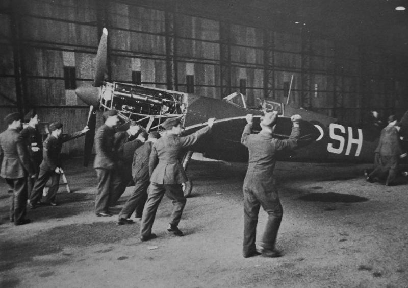 Истребитель Supermarine Spitfire закатывают в ангар с неполадкой двигателя. 1940 г.