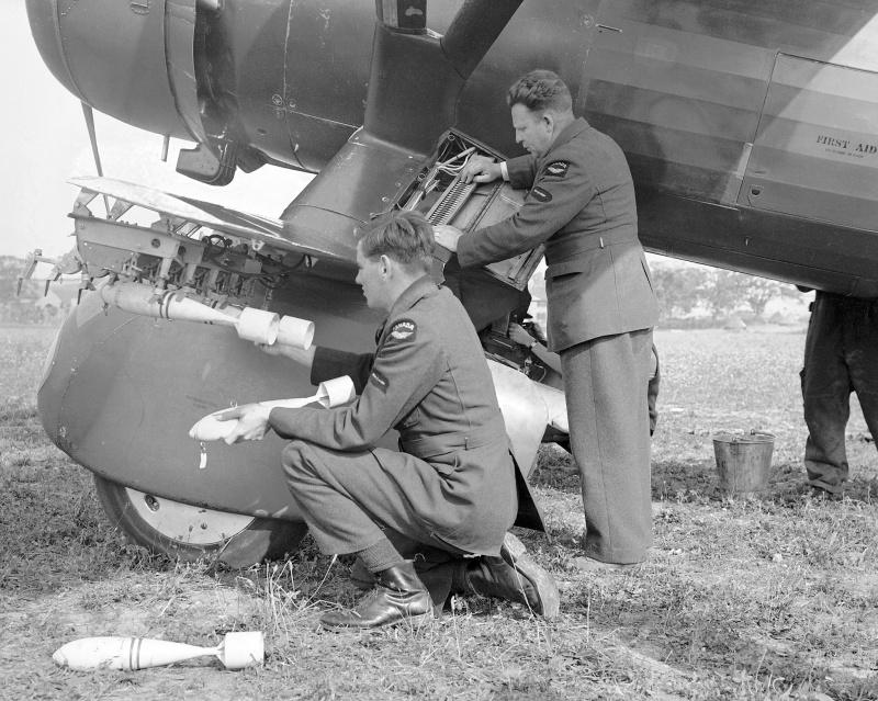 Оружейники подвешивают бомбы и заряжают курсовой пулемет. 1940 г.