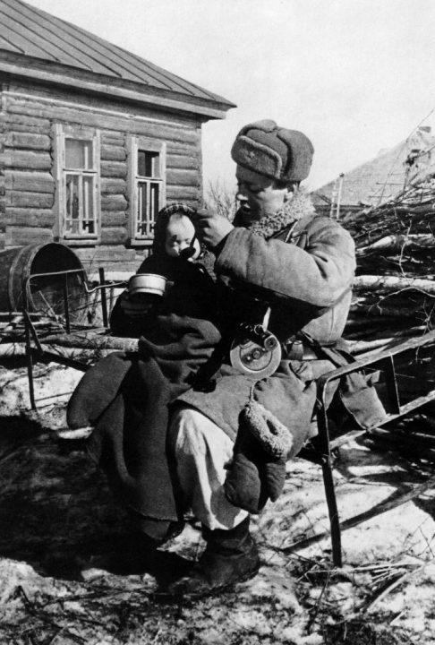 Старший сержант Моисеев кормит сироту в освобожденной деревне Извеково. Март 1943 г.