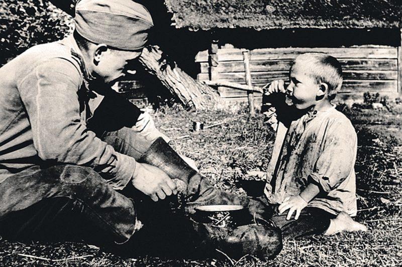 Красноармеец кормит ребенка. Вильнюсская область, июнь 1944 г.
