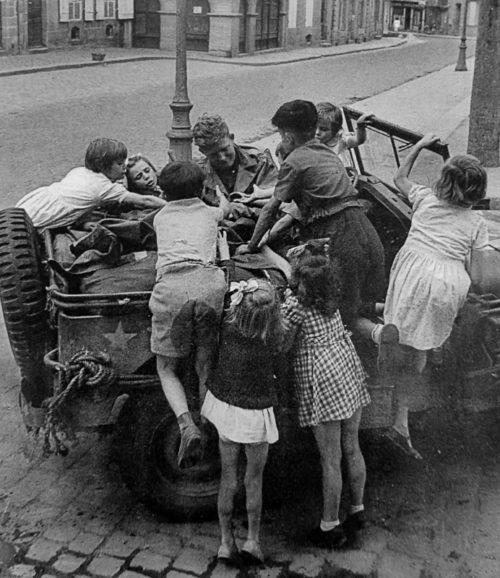 Американский солдат раздает шоколад детям в Динаре. Франция,1944 г.