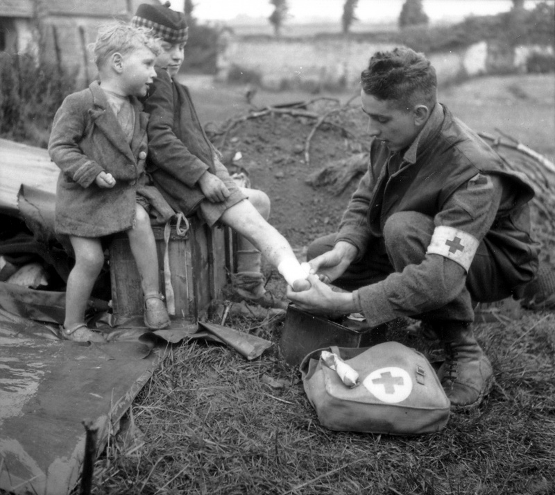 Американские медики и раненые французские дети в полевом госпитале. Июнь 1944 г.
