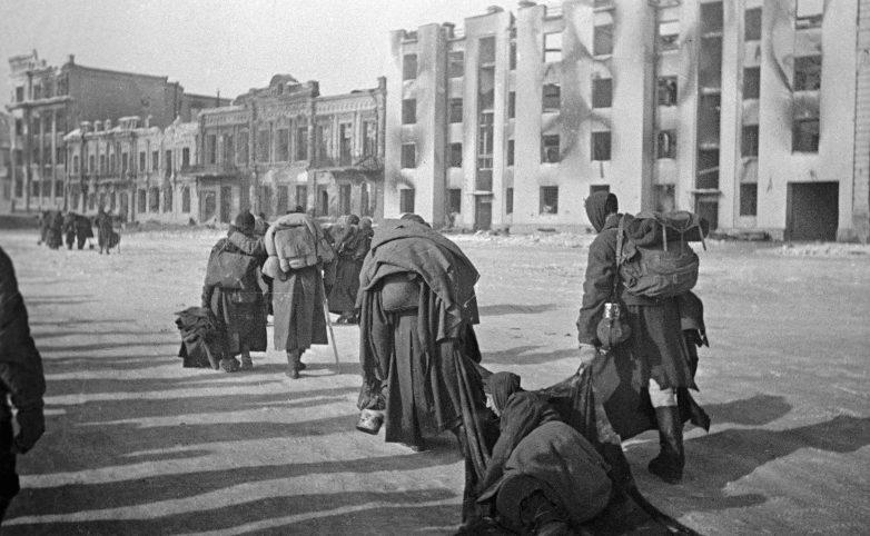 Немецкие военнопленные в Сталинграде везут раненого на плащ-палатке. 1943 г.