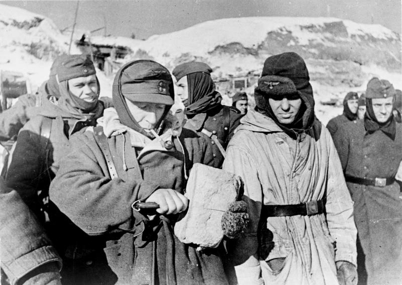 Немецкие пленные, захваченные под Сталинградом, делят хлеб. 1943 г.