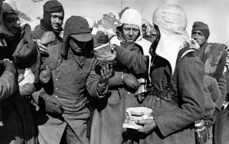 Немецкий солдат раздает своим товарищам, плененным под Сталинградом, нарезанный хлеб. 1943 г.