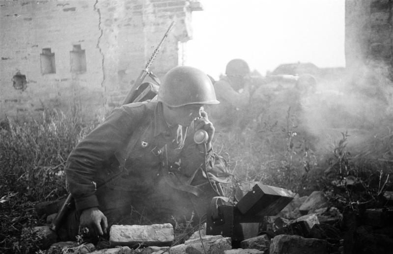 Советский связист у полевого телефона во время уличных боев. Август 1942 г.
