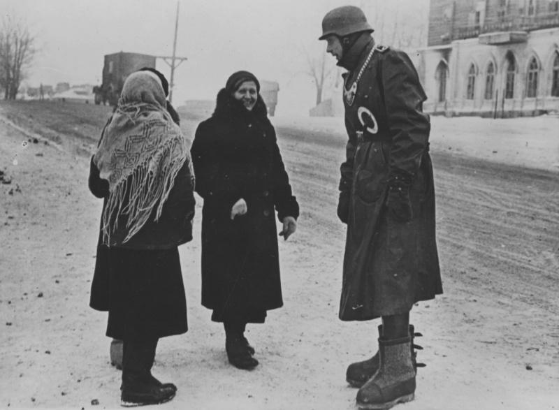 Солдат полевой жандармерии с женщинами на улице города. Ноябрь 1941 г.