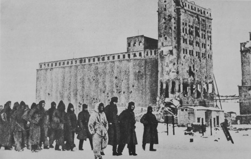 Красноармеец конвоирует колонну немецких военнопленных у здания элеватора в Сталинграде. 1943 г.