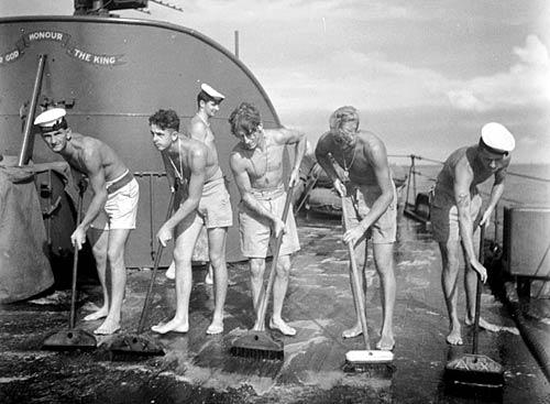 Матросы драят палубу крейсера Хобарт. Северный Борнео, июнь 1945 г.
