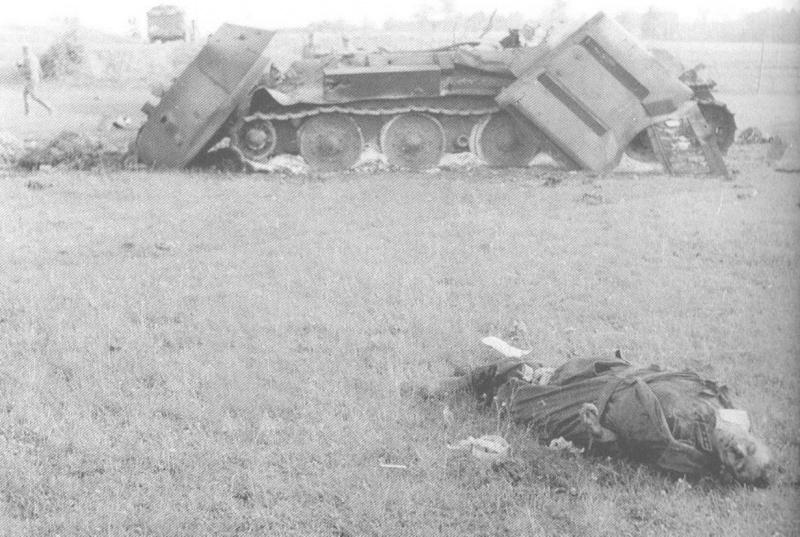 Уничтоженный танк Т-34 и погибший командир танка. 25 июня 1941 г.