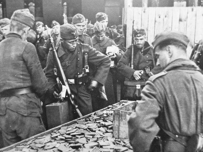 Немецкие солдаты сдают патроны на железнодорожном вокзале перед отправлением в отпуск. Сентябрь 1942 г.