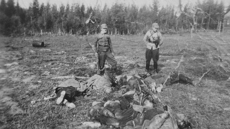 Финские солдаты у тел расстрелянных советских военнопленных. Октябрь 1941 г.