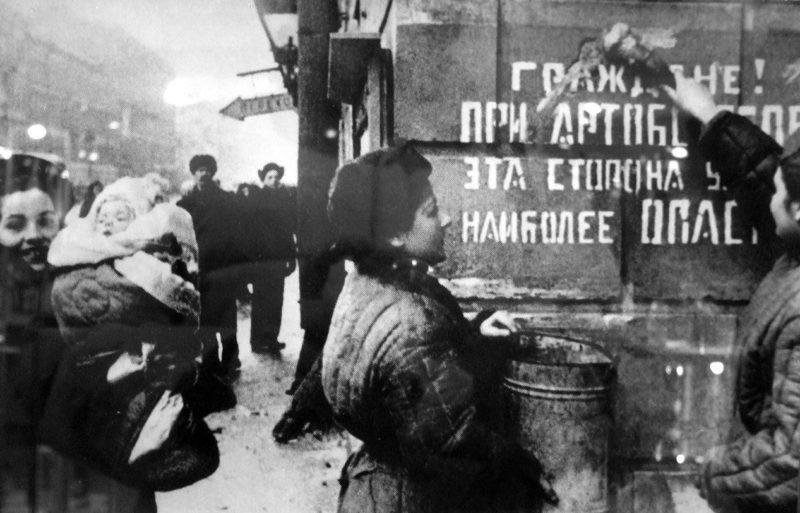 Ленинградцы закрашивают надпись «Граждане! При артобстреле эта сторона улицы наиболее опасна». Январь 1944 г.