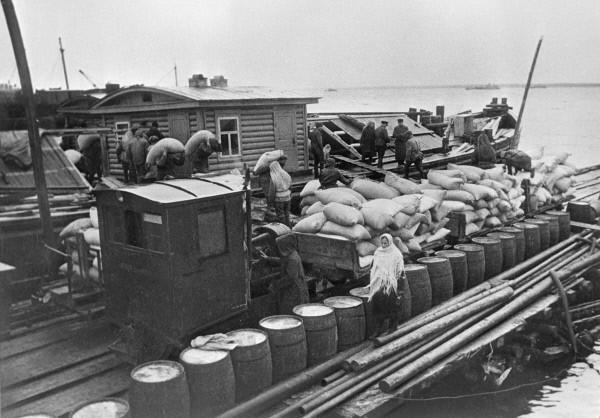Перегрузка грузов с баржи на узкоколейную железную дорогу на причале.